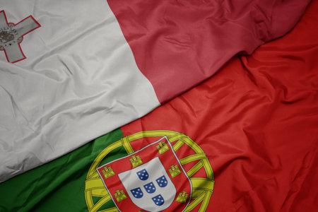 waving colorful flag of portugal and national flag of malta. macro