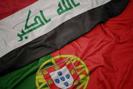 waving colorful flag of portugal and national flag of iraq. macro