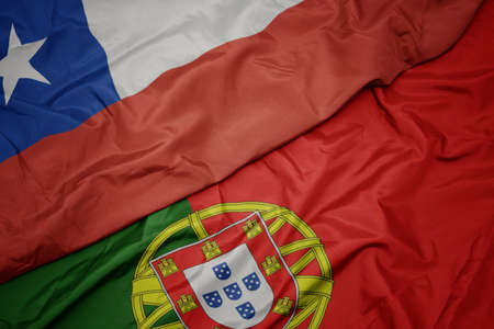waving colorful flag of portugal and national flag of chile. macro