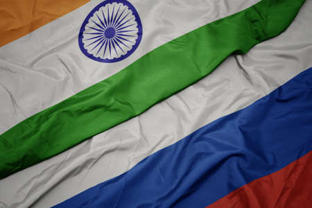 waving colorful flag of russia and national flag of india. macro