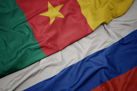 waving colorful flag of russia and national flag of cameroon. macro