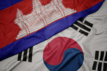 waving colorful flag of south korea and national flag of cambodia. macro