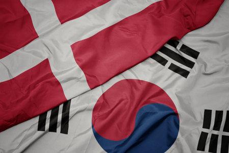 waving colorful flag of south korea and national flag of denmark. macro