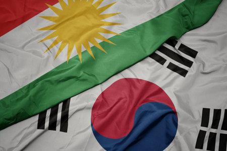waving colorful flag of south korea and national flag of kurdistan. macro