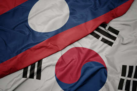 waving colorful flag of south korea and national flag of laos. macro