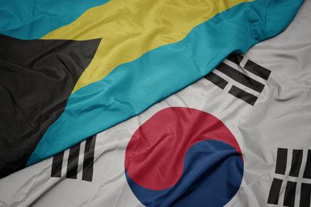waving colorful flag of south korea and national flag of bahamas. macro