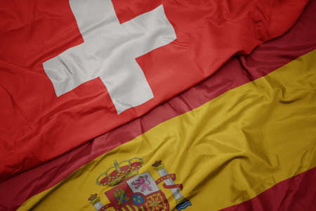 waving colorful flag of spain and national flag of switzerland. macro