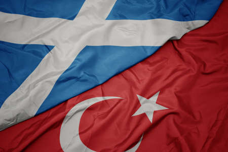 waving colorful flag of turkey and national flag of scotland. macro