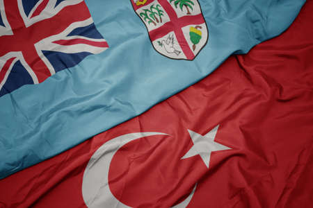 waving colorful flag of turkey and national flag of Fiji. macro