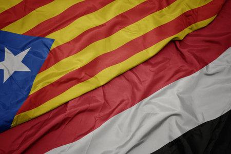 waving colorful flag of yemen and national flag of catalonia. macro