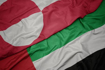 waving colorful flag of united arab emirates and national flag of greenland. macro