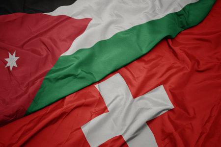 waving colorful flag of switzerland and national flag of jordan. macro