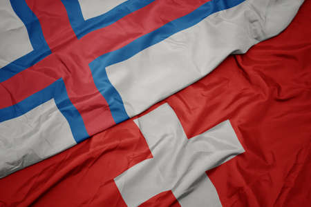 waving colorful flag of switzerland and national flag of faroe islands. macro