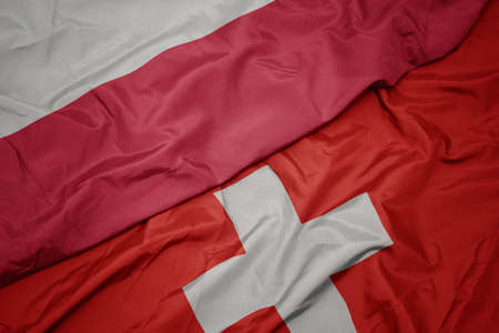 waving colorful flag of switzerland and national flag of poland. macro