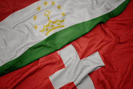 waving colorful flag of switzerland and national flag of tajikistan. macro