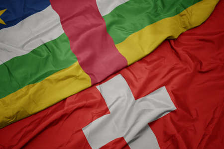 waving colorful flag of switzerland and national flag of central african republic. macro