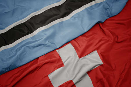 waving colorful flag of switzerland and national flag of botswana. macro