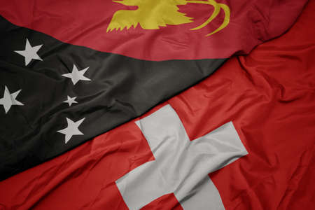 waving colorful flag of switzerland and national flag of Papua New Guinea. macro