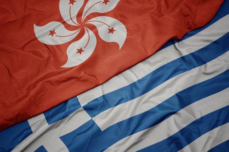 waving colorful flag of greece and national flag of hong kong. macro