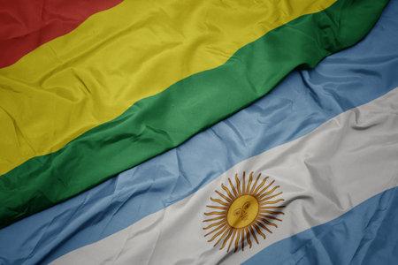 waving colorful flag of argentina and national flag of bolivia. macro