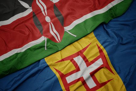 waving colorful flag of madeira and national flag of kenya. macro Stock Photo