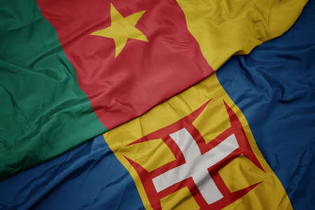 waving colorful flag of madeira and national flag of cameroon. macro