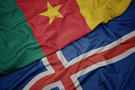waving colorful flag of iceland and national flag of cameroon. macro