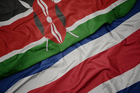 waving colorful flag of costa rica and national flag of kenya. macro Stock Photo