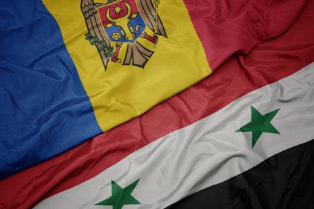 waving colorful flag of syria and national flag of moldova. macro