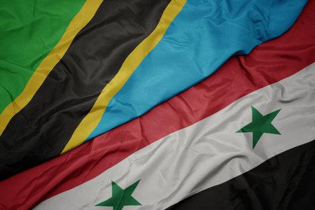 waving colorful flag of syria and national flag of tanzania. macro