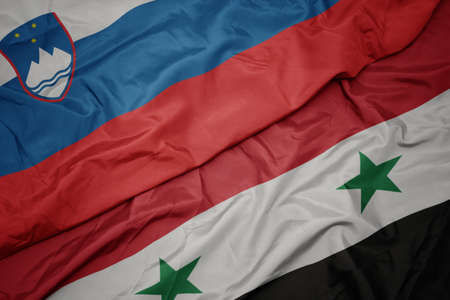 waving colorful flag of syria and national flag of slovenia. macro
