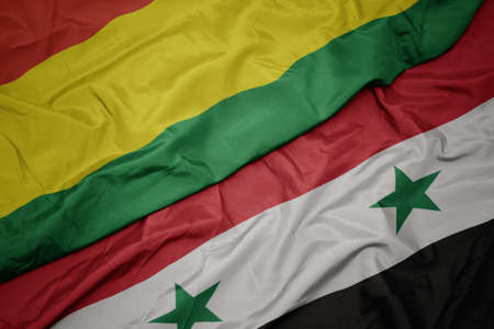 waving colorful flag of syria and national flag of bolivia. macro