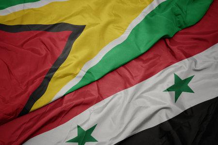waving colorful flag of syria and national flag of guyana. macro