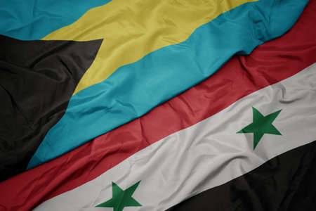 waving colorful flag of syria and national flag of bahamas. macro