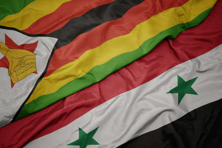 waving colorful flag of syria and national flag of zimbabwe. macro