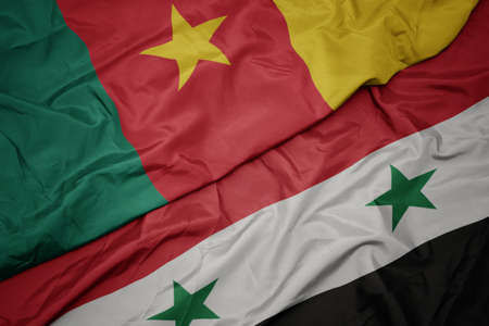 waving colorful flag of syria and national flag of cameroon. macro