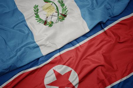 waving colorful flag of north korea and national flag of guatemala. macro