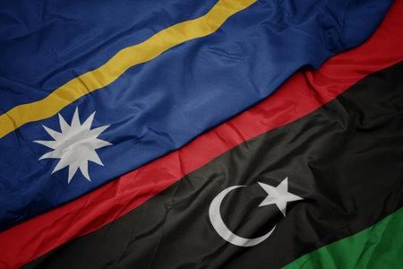 waving colorful flag of libya and national flag of Nauru . macro