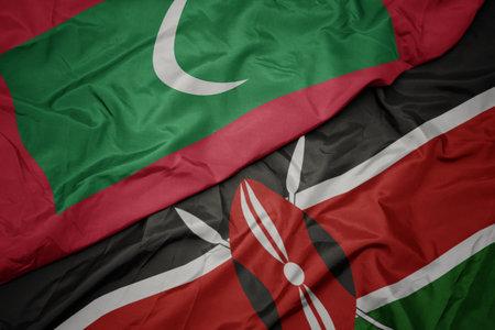 waving colorful flag of kenya and national flag of maldives. macro