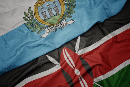 waving colorful flag of kenya and national flag of san marino. macro