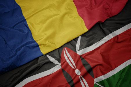 waving colorful flag of kenya and national flag of romania. macro