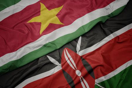 waving colorful flag of kenya and national flag of suriname. macro Stock Photo