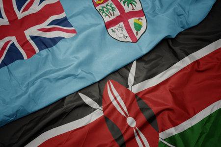 waving colorful flag of kenya and national flag of Fiji . macro