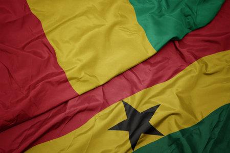 waving colorful flag of ghana and national flag of guinea. macro Stock Photo