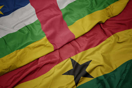 waving colorful flag of ghana and national flag of central african republic. macro