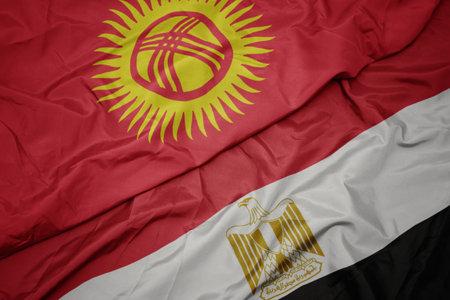 waving colorful flag of egypt and national flag of kyrgyzstan. macro