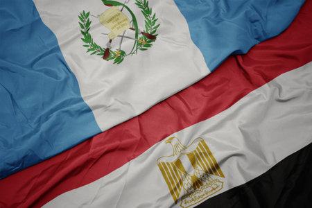 waving colorful flag of egypt and national flag of guatemala. macro Stock Photo
