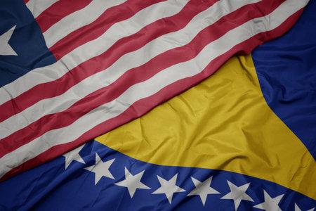 waving colorful flag of bosnia and herzegovina and national flag of liberia. macro