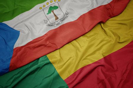 waving colorful flag of benin and national flag of equatorial guinea. macro
