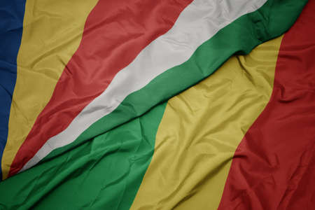 waving colorful flag of republic of the congo and national flag of seychelles. macro Stock Photo